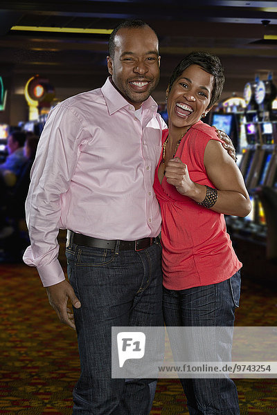 Excited couple standing in casino