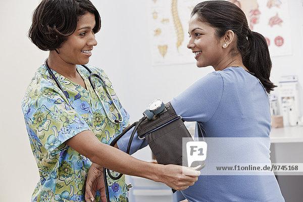 Nurse taking pregnant woman's blood pressure