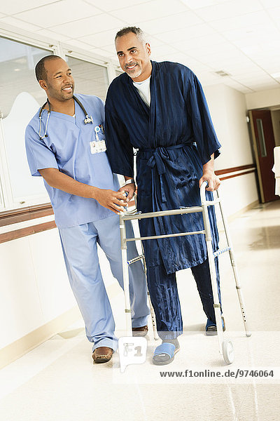 Nurse helping patient use walker in hospital