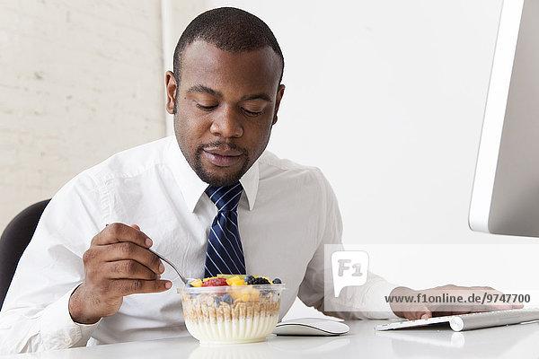 Schreibtisch Geschäftsmann schwarz essen essend isst Frühstück
