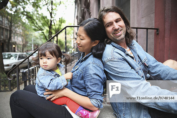 Family sitting on front stoop in city