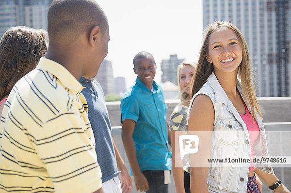 Smiling teenagers walking on urban rooftop