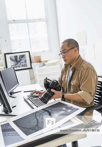 Korean photographer using computer at desk