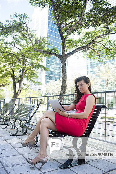Caucasian businesswoman using digital tablet on urban park bench