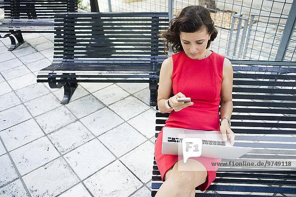 Handy benutzen Europäer Geschäftsfrau Notebook Sitzbank Bank