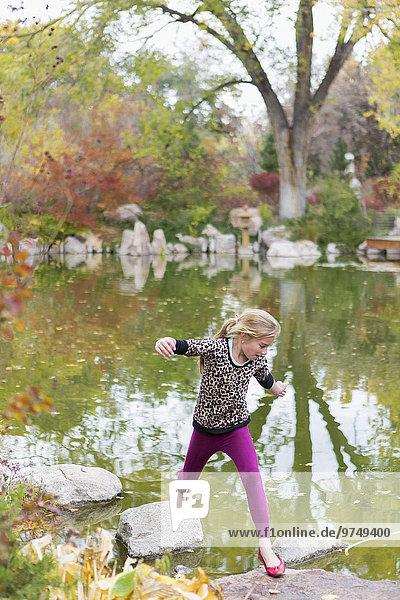 Caucasian girl jumping on rocks in pond
