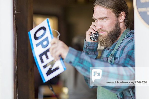 Caucasian server on telephone hanging open sign on cafe window