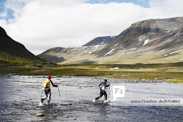 Hikers crossing mountain river