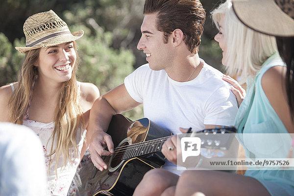 Glückliche Freunde mit der Gitarre im Freien