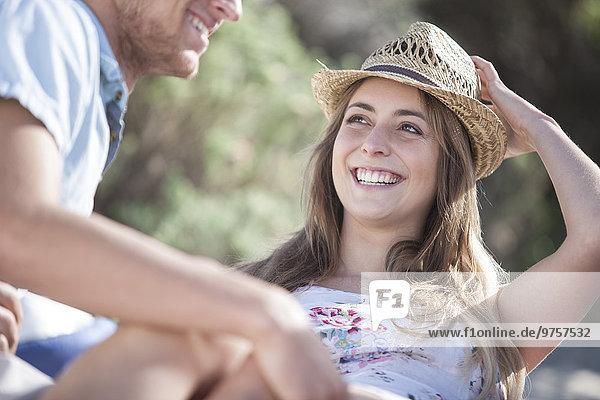 Lächelnde junge Frau  die den Mann im Freien ansieht.