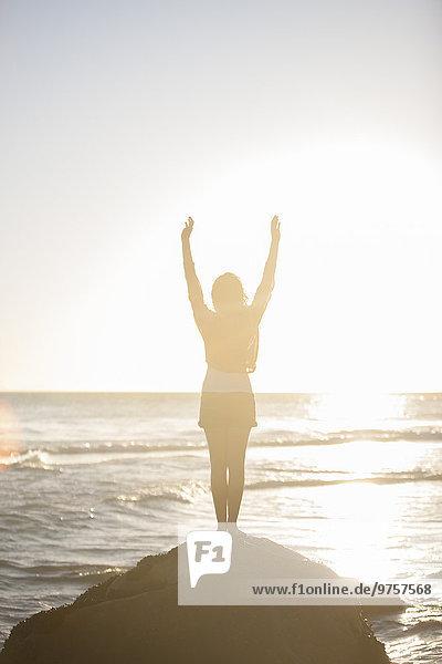 Junge Frau steht bei Sonnenuntergang auf einem Felsen am Strand.