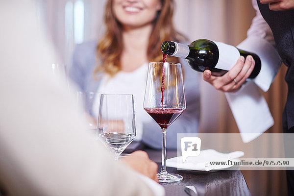Kellnerin beim Weinschenken für Geschäftspartner im Hotelrestaurant