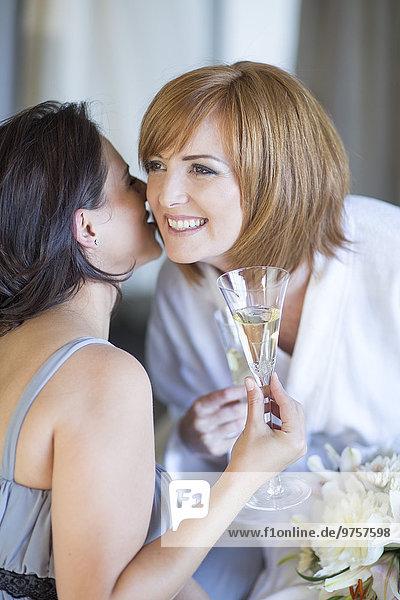 Braut und Brautjungfer trinkt Sektgläser und bereitet sich auf die Hochzeit vor.