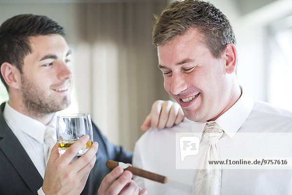 Groom smoking a cigar with best man before wedding