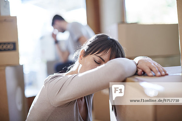 Couple moving house  woman resting on a box