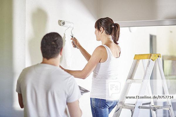 Ein Paar streicht die Wand im neuen Zuhause.