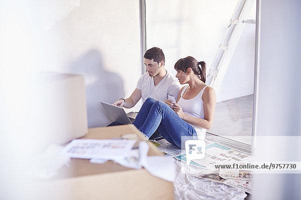 Paar mit Laptop bei der Renovierung eines neuen Hauses