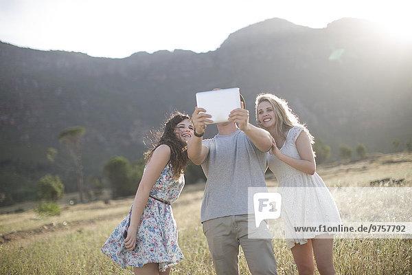 Südafrika  Freunde beim Selbstfotografieren mit Tablett im Feld