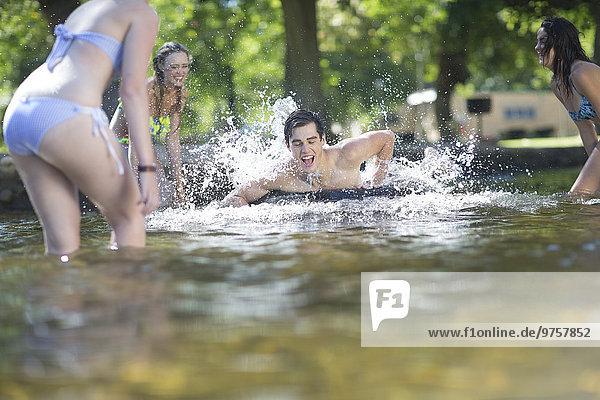 Freunde im Urlaub haben Spaß mit Schlauch im Pool