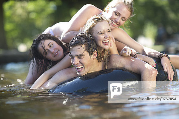 Friends on holiday having fun with inner tube in a pool