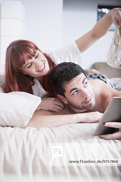 Junges Paar im Bett liegend Frau zeigt Mann ihre Dessous
