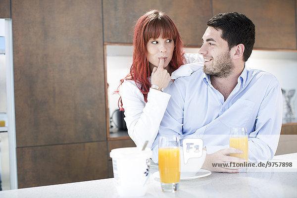 Paar in der Küche beim Frühstück mit Orangensaft