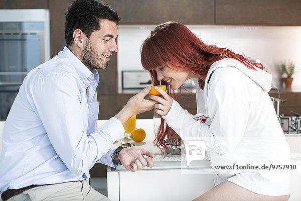 Paar in der Küche macht frischen Orangensaft