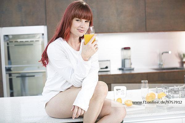Frau sitzt auf der Küchentheke mit frisch zubereitetem Orangensaft