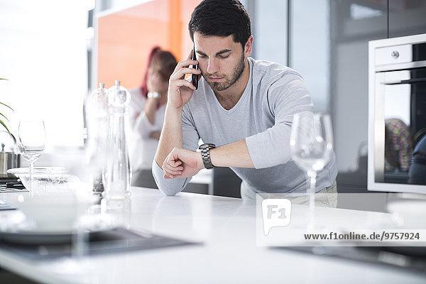Mann in der Küche überprüft die Zeit und spricht mit dem Handy
