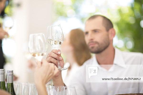 Mann bei der Untersuchung von Weißwein bei einer Weinprobe