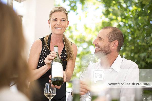 Frau präsentiert Flasche Wein bei einer Weinprobe