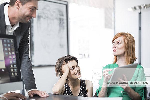 Geschäftsfrau zeigt Kollegen digitales Tablett
