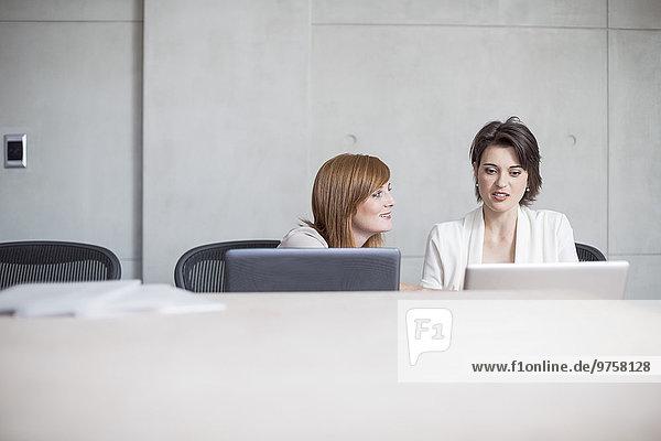 Zwei Geschäftsfrauen mit Laptops im Konferenzraum