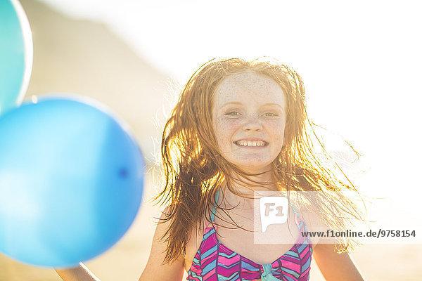 Mädchen am Strand lächelt und hält Luftballons