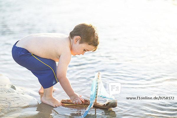 Junge am Strand spielt mit einem Spielzeug-Holzboot im Wasser