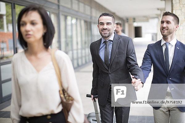 Schwules Paar  das mit Geschäftsanzügen reist