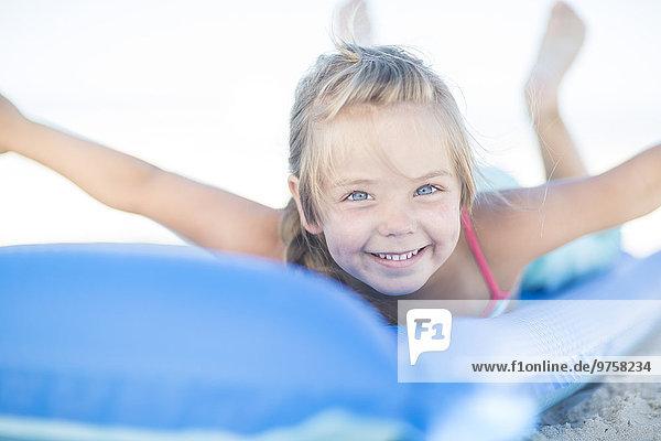 Lächelndes Mädchen am Strand auf einer Lilo liegend Lächelndes Mädchen am Strand auf einer Lilo liegend