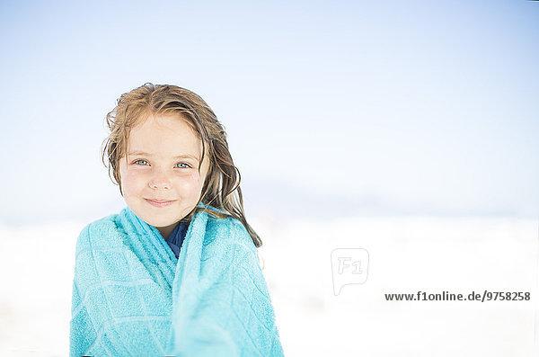 Lächelndes Mädchen am Strand in ein Handtuch gewickelt Lächelndes Mädchen am Strand in ein Handtuch gewickelt