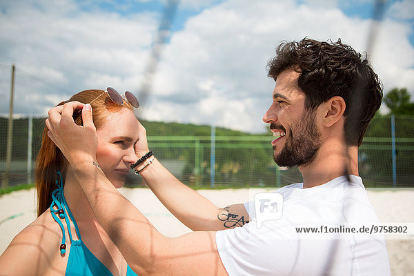 Junges Paar auf dem Beachvolleyballfeld