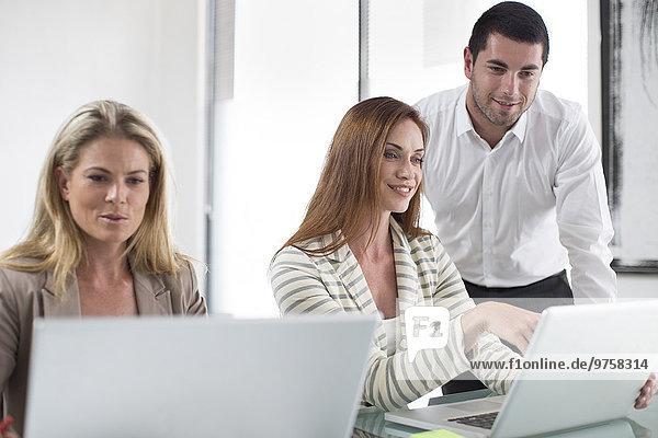 Geschäftsfrauen und Geschäftsleute im Büro bei der Arbeit an Laptops