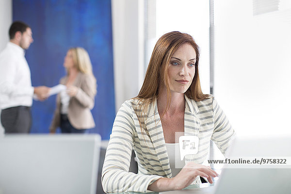 Geschäftsfrau im Büro bei der Arbeit am Laptop