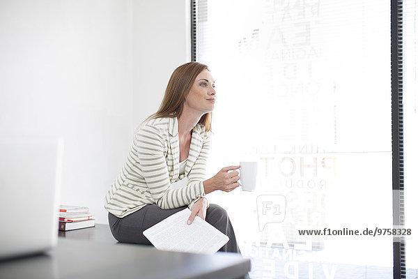 Geschäftsfrau im Büro mit Kaffeetasse