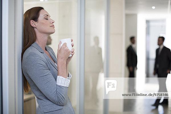 Geschäftsfrau bei einer Kaffeepause im Bürogeschoss