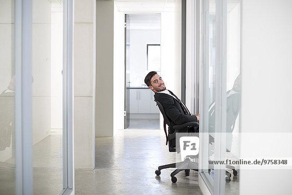 Geschäftsmann im Anzug sitzt auf einem Stuhl und lehnt sich in den Flur.