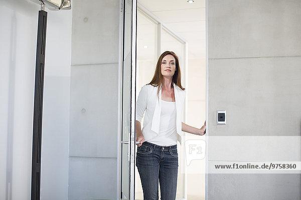 Lässig gekleidete Geschäftsfrau öffnet Vorstandstür
