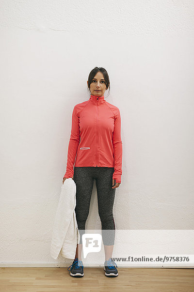Junge Frau mit Handtuch im Trainingsanzug