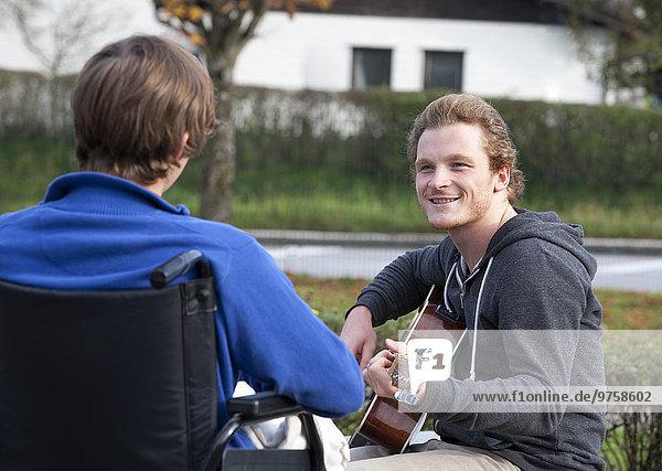 Junge Rollstuhlfahrer hören Gitarristin