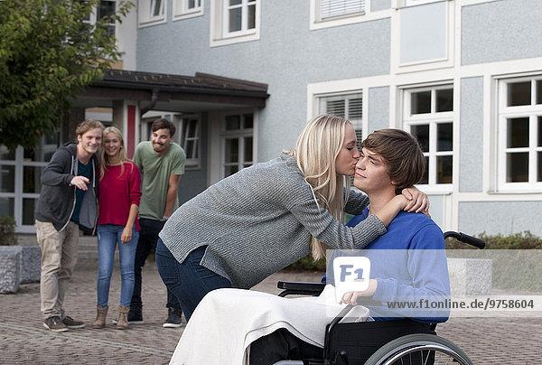 Junge Frau  die ihren Freund im Rollstuhl küsst