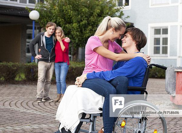Junge Frau  die ihren Freund im Rollstuhl umarmt
