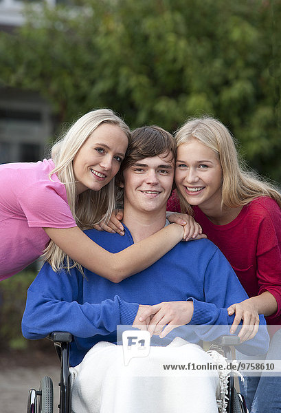 Gruppenbild eines Mädchens und einer jungen Frau mit ihrem Freund im Rollstuhl